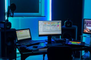 Studio in the dark with multiple monitors and big speakers